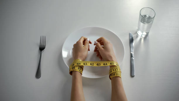 Hands tied with tapeline on empty plate, girl obsessed with counting calories Hands tied with tapeline on empty plate, girl obsessed with counting calories anorexia nervosa stock pictures, royalty-free photos & images