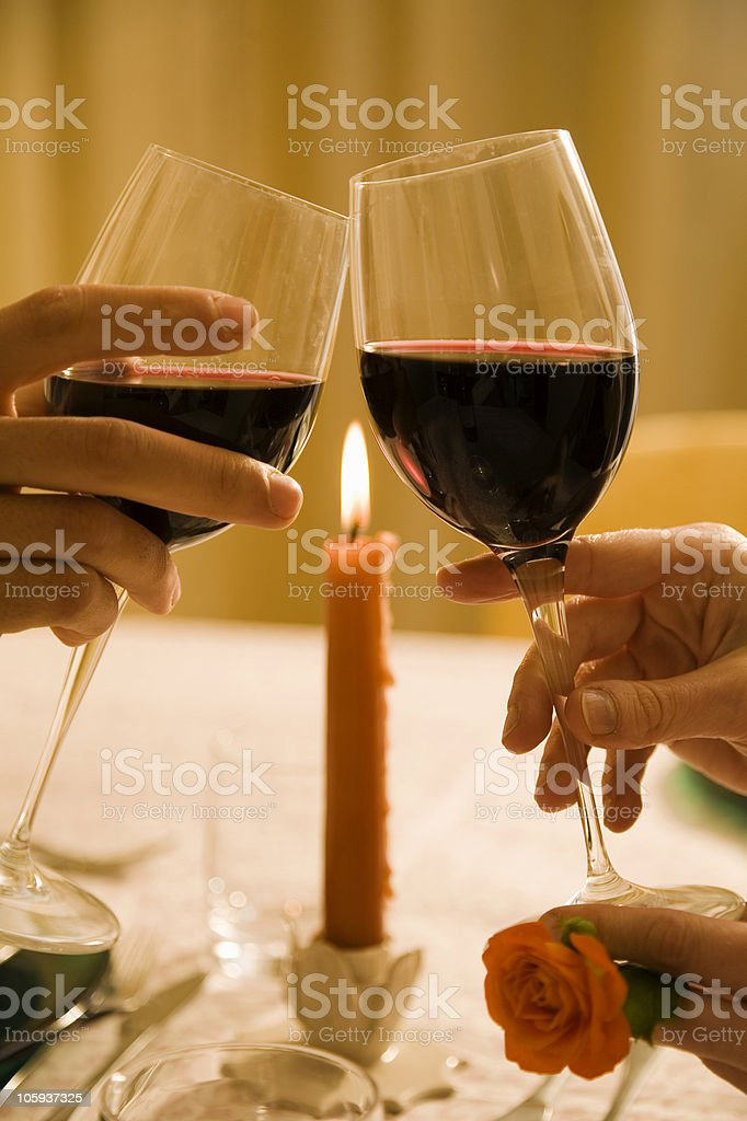 Hands toasting with red wine glasses on a candle lit dinner royalty-free stock photo