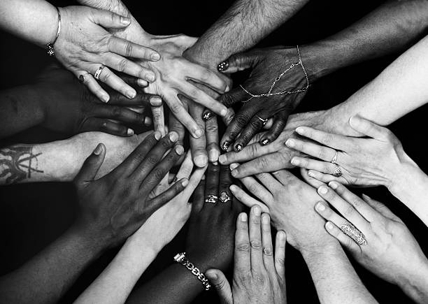 Hands together Male and female hands of various ethnicities all together. Monochrome. human rights stock pictures, royalty-free photos & images