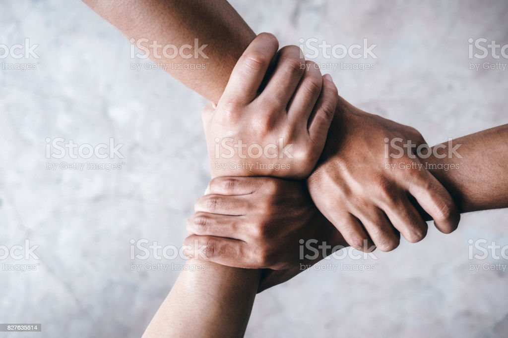 Hands together  showing teamwork. Close up top view of young people putting their hands together showing unity and teamwork. Above Stock Photo