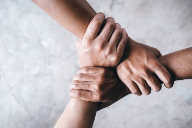 hands together  showing teamwork. - unity stock pictures, royalty-free photos & images