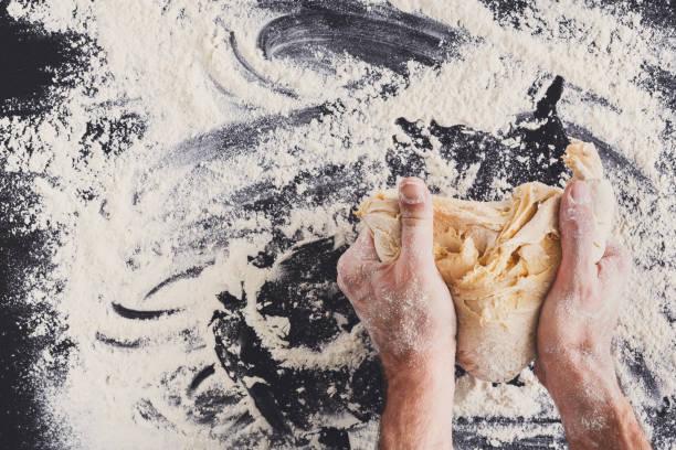 hands top view knead dough on black background - impastare foto e immagini stock