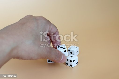 istock Hands trying to pick up the dice on a soft brown background. 1031196422