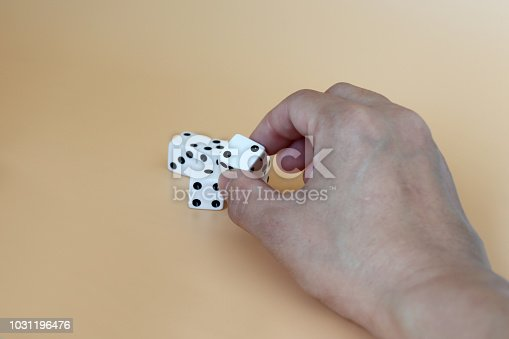 istock Hands trying to pick up the dice on a soft brown background. 1031196476