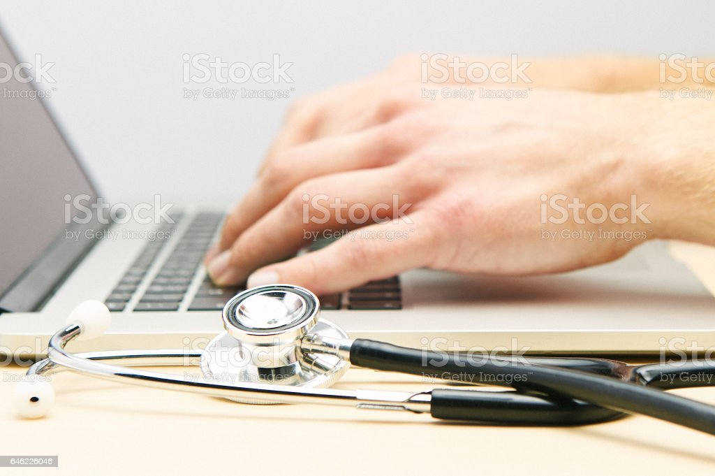 Hands typing on a laptop with a stethoscope in the foreground. stock photo