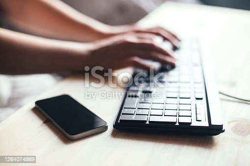 Closeup of a female hands busy typing on a computer. Hands using computer keyboard and phone for online shopping
