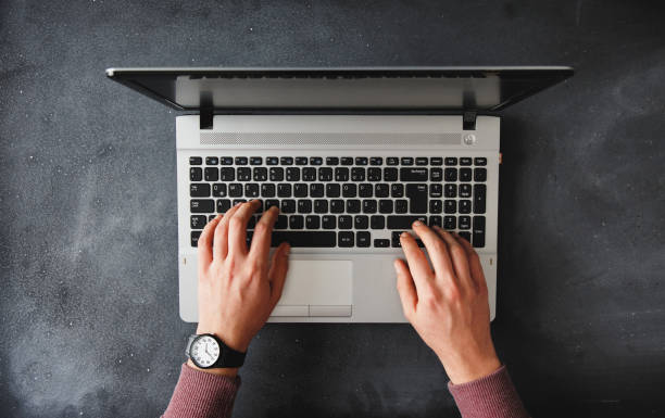 Hands typing on laptop above stock photo