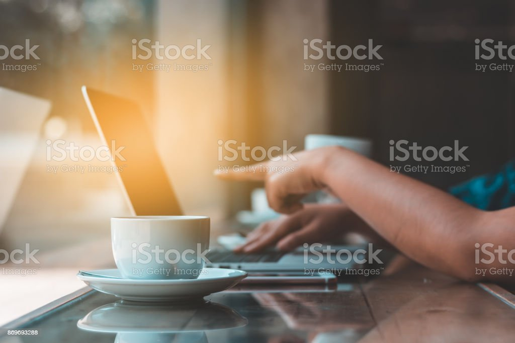 Hands typing on laptop in coffee shop stock photo