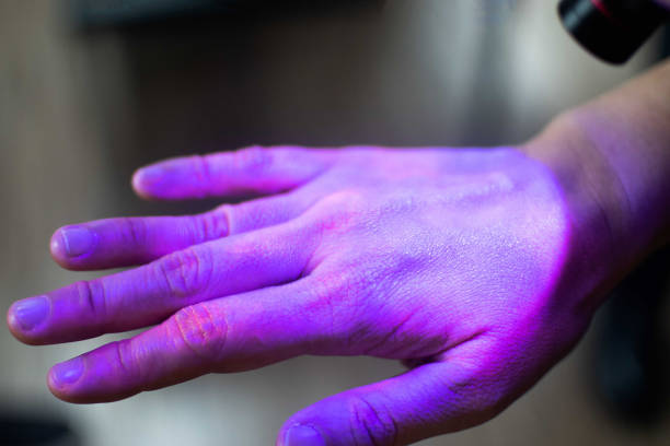 hands under black uv light to detect glow in the dark germs around nails and fingerprint as visual tool for teaching proper handwashing, aseptic techniques, and general infection control - handwashing stock photos and pictures
