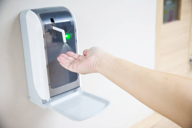 Hands under the automatic alcohol dispenser. stock photo