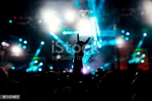 istock Hands up in the air raised crowd arms. Silhouette people having fun at club party concert. 921424822