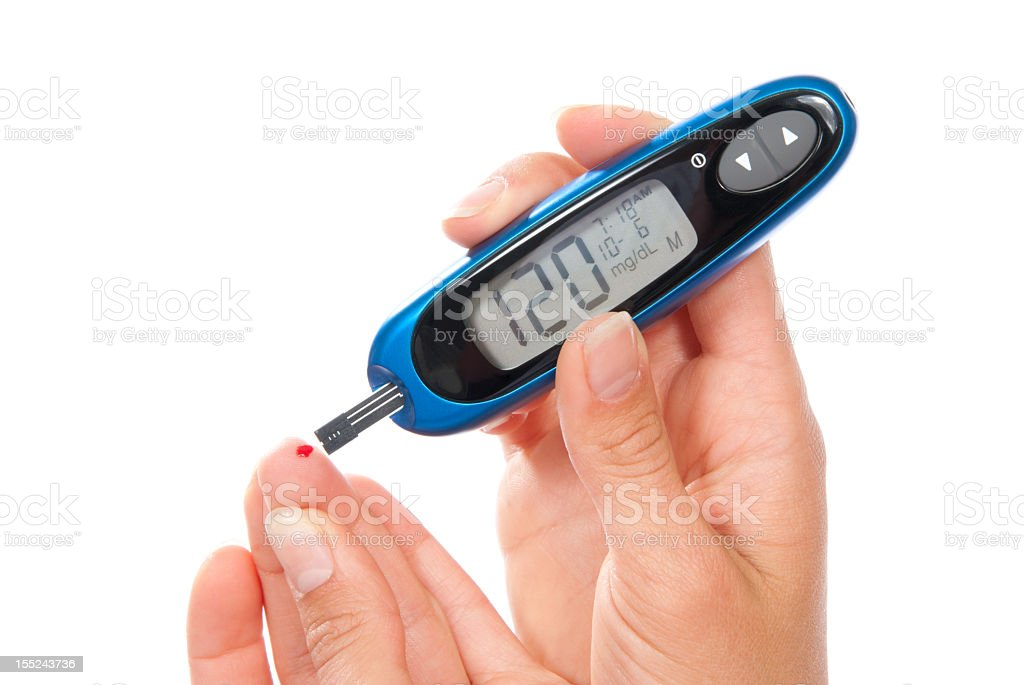 Hands using a blood test for diabetes stock photo