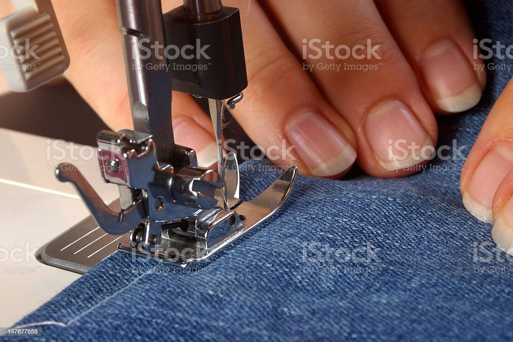 Hands using a sewing machine stock photo