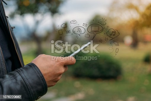 831899586istockphoto Hands using mobile phone, with technology icons 1076220682