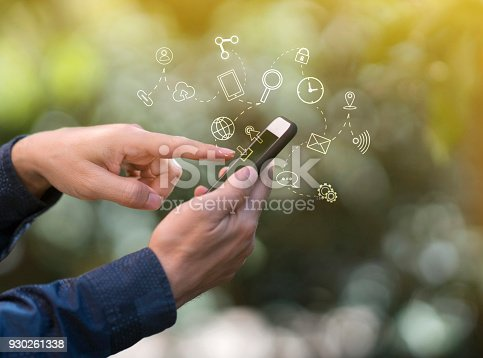 831899586istockphoto Hands using mobile phone, with technology icons 930261338