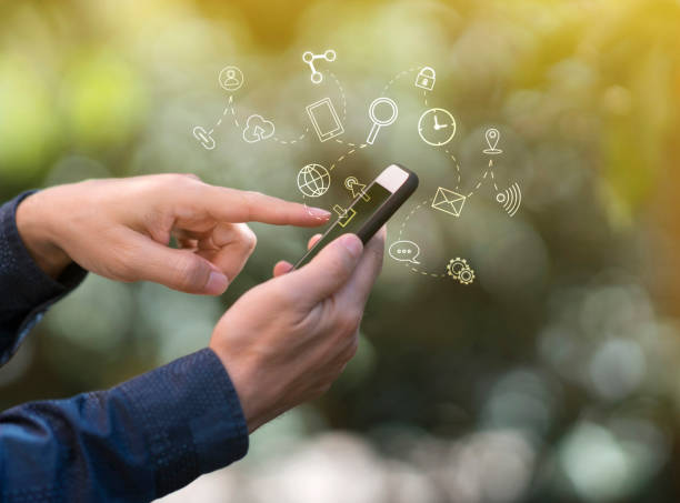 Hands using mobile phone, with technology icons stock photo