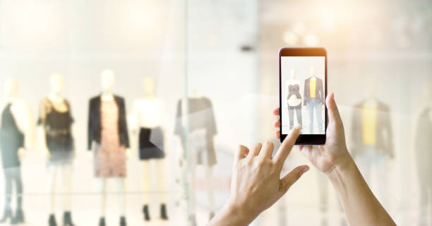 hands using mobile smart phone and take a photo in display view of a clothing store, shopping online concept - store window stock pictures, royalty-free photos & images