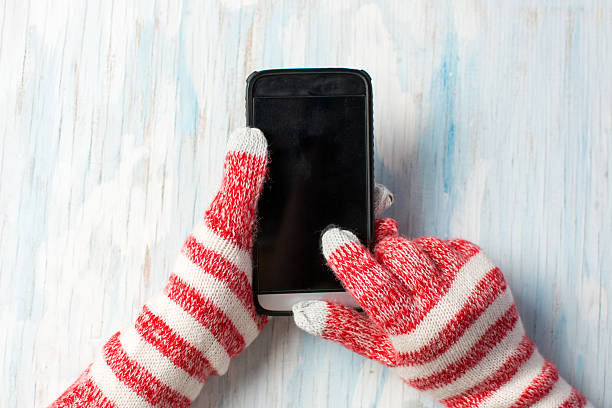 Hands using phone in winter gloves