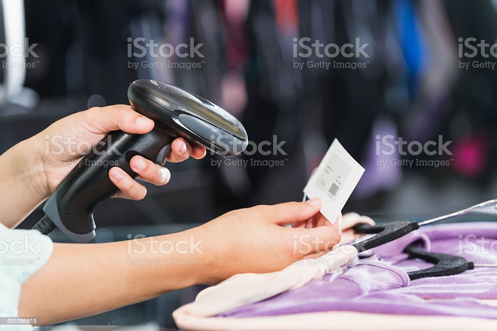 Hands using scanner to scan price tag in clothing store stock photo
