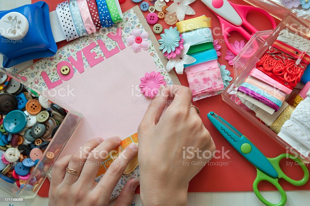 Hands using scrapbooking tools with the word lovely stock photo