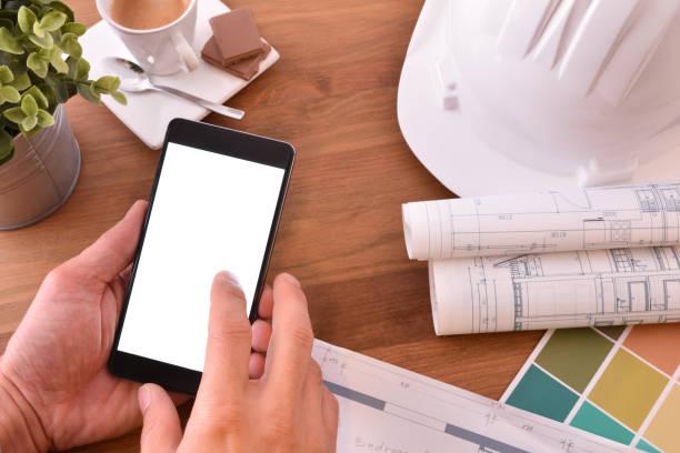 Manos con smartphone en oficina de un arquitecto - foto de stock