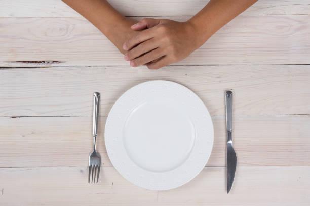 händer med sked och gaffel, äta koncept. - bordsskick bildbanksfoton och bilder