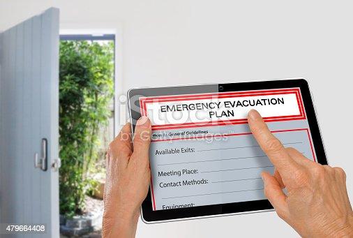Hands using Tablet with Emergency Evacuation Plan beside Exit Door