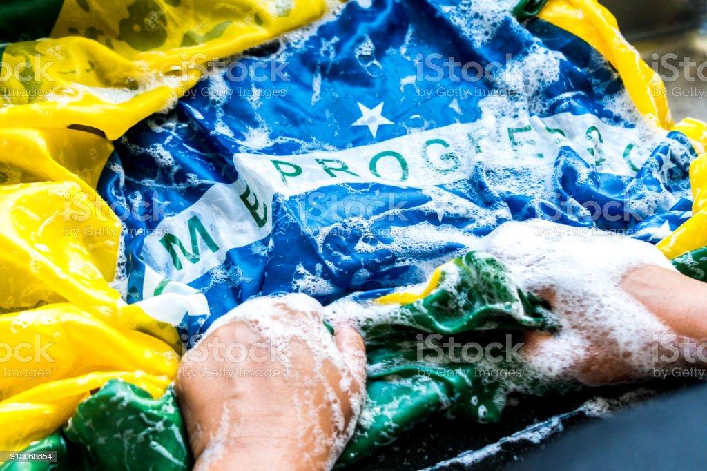 Hands Washing Brazilian Flag - New Brazil/Corruption Concept stock photo