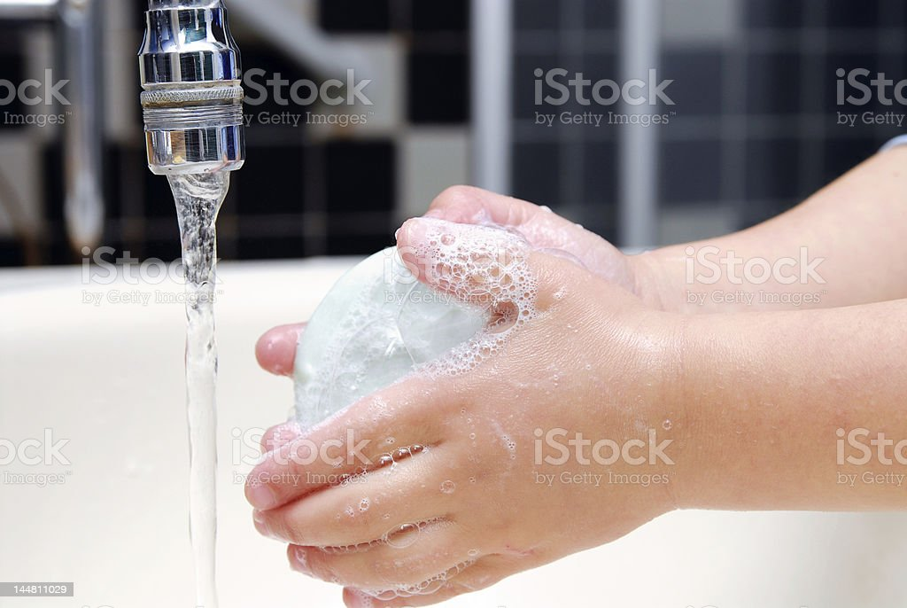 Hands washing with a bar of soap under the faucet stock photo