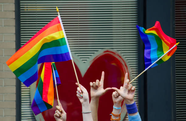 hands waving gay flags - transsexual stock photos and pictures