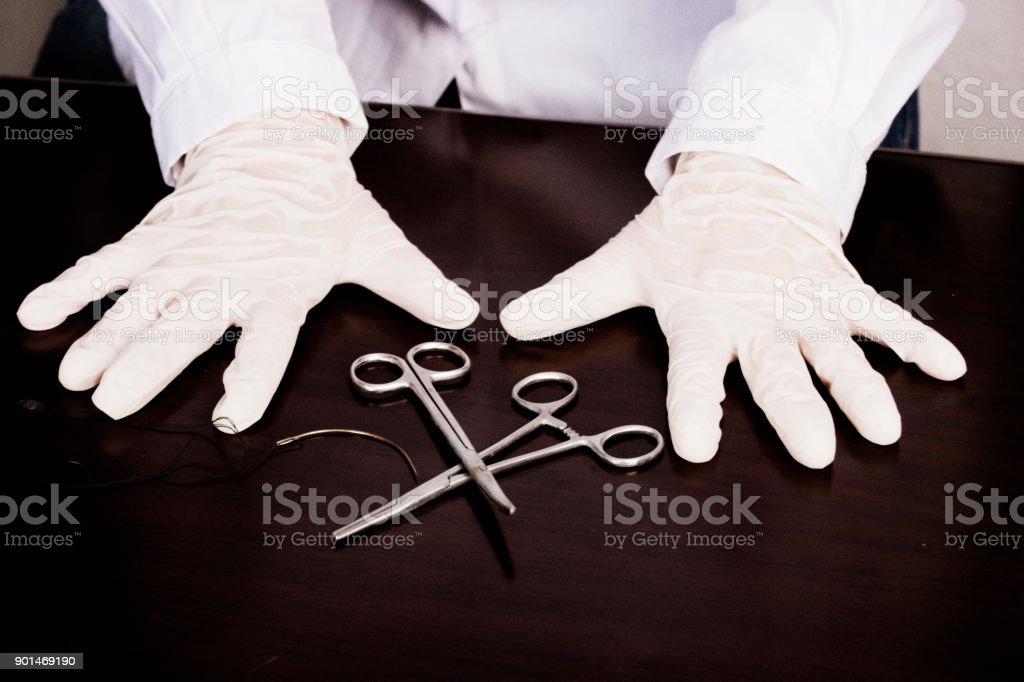 Hands wearing latex gloves examines medical forceps stock photo