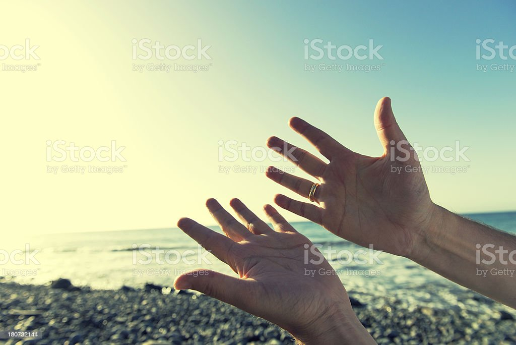 Hands welcoming the sun on a beach royalty-free stock photo
