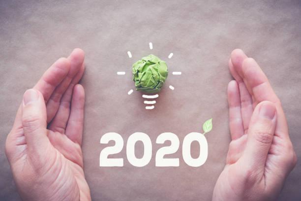 hands with 2020 green paper light bulb, new year eco, social responsibility, csr, innovation solution concept - rifiuti zero foto e immagini stock