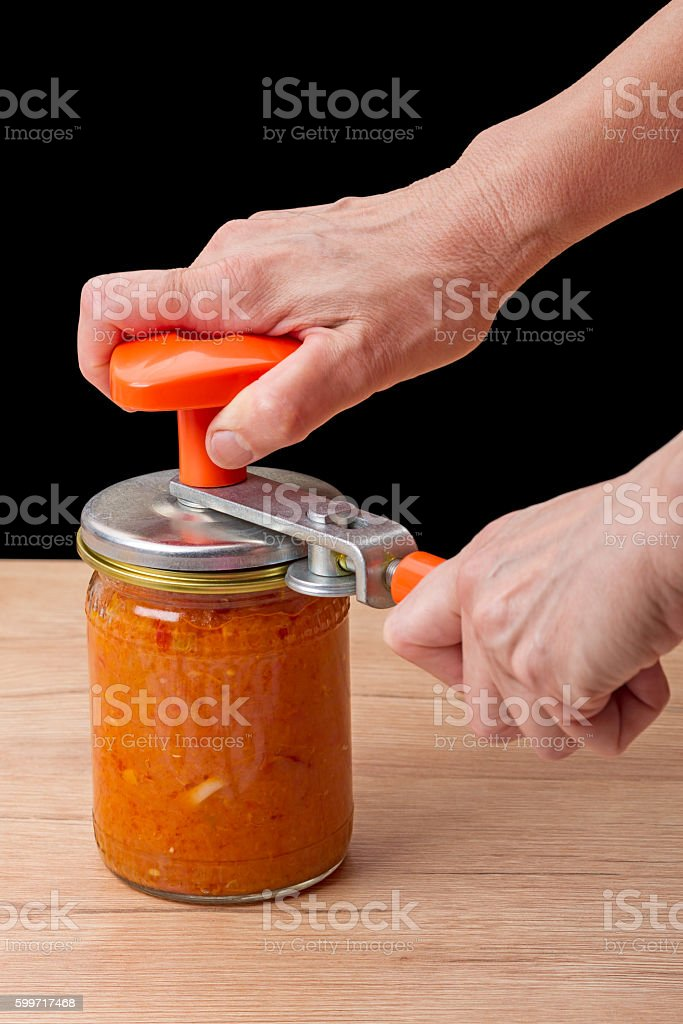 Hands with a device for closing cans stock photo
