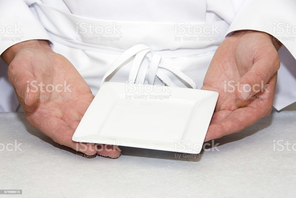 Hands with a single empty square plate stock photo