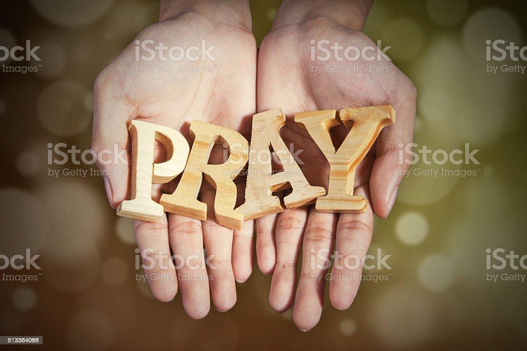 Manos con una palabra de rezar de fondo bokeh - foto de stock