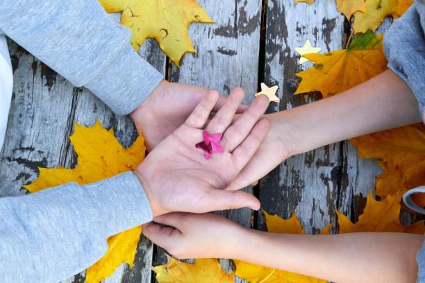 Manos con hojas de otoño sobre fondo de madera - foto de stock