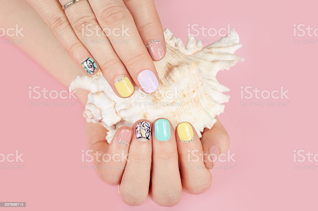 Hands with beautiful manicured nails and sea shell stock photo