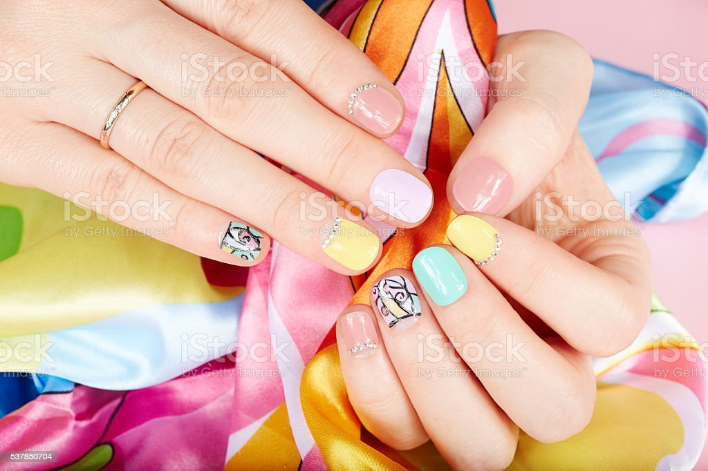 Hands with beautiful manicured nails different colored with nail...