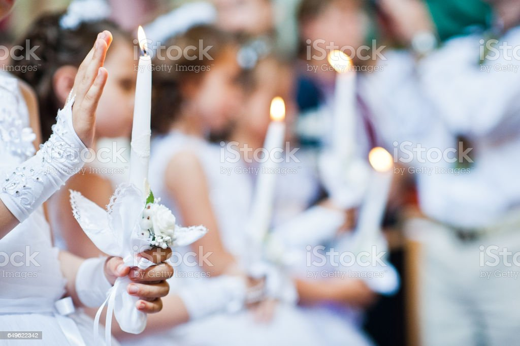 Hands with candles of little girls on first holy communion stock photo