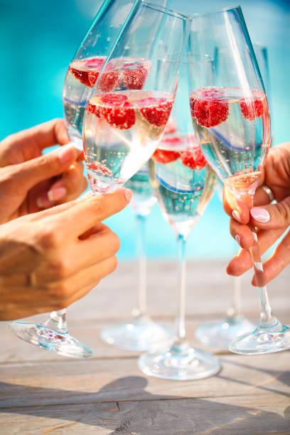 Mains avec des verres de Champagne avec framboise - Photo