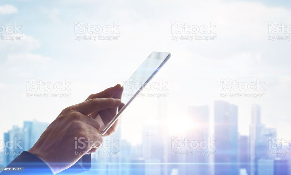 Hands with digital tablet on blurred city background stock photo