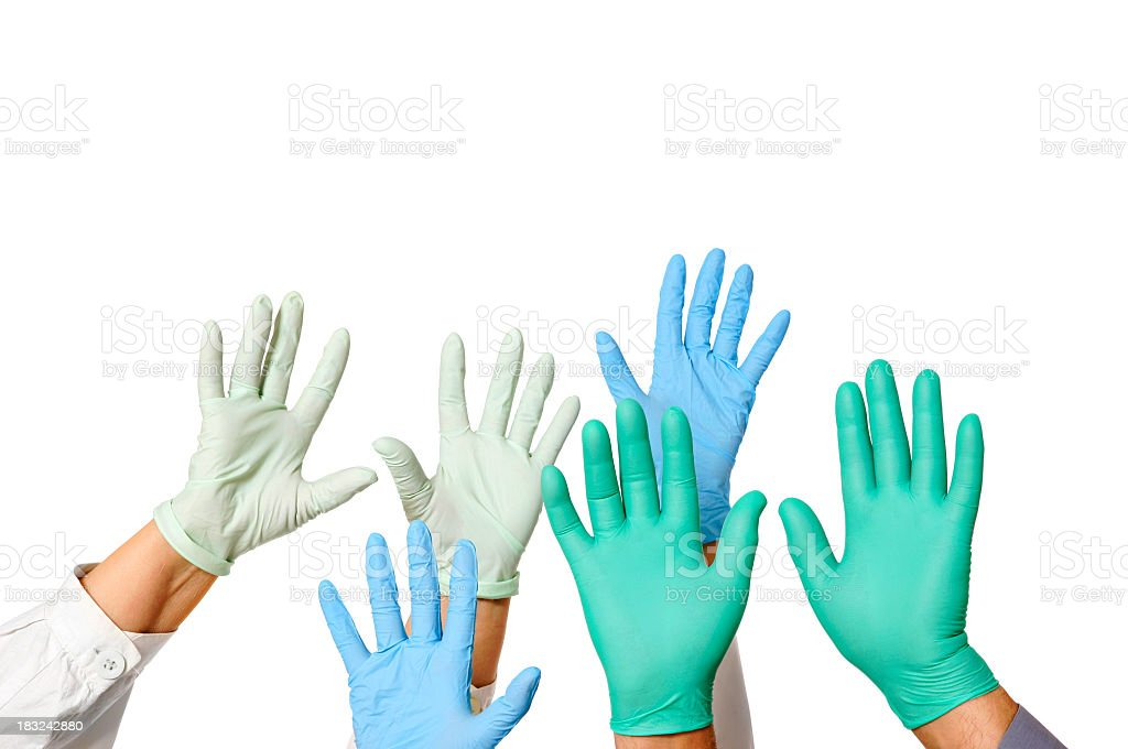 Hands with doctor rubber gloves in green, blue, and white stock photo