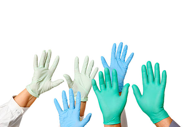 Hands with doctor rubber gloves in green, blue, and white Many doctors hands in gloves, isolated on white. surgical glove stock pictures, royalty-free photos & images