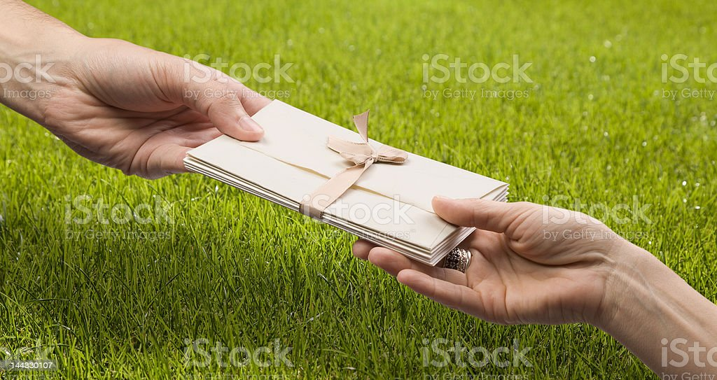 Hands with envelopes on green grass royalty-free stock photo