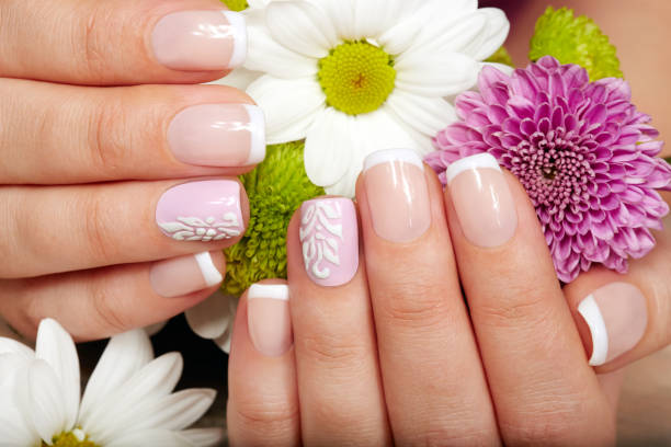 Hands with french manicured nails and flowers stock photo