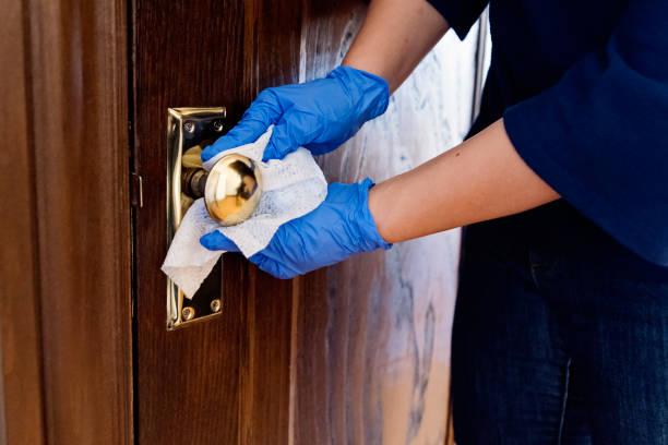 Hands with glove wiping doorknob on wooden door. stock photo