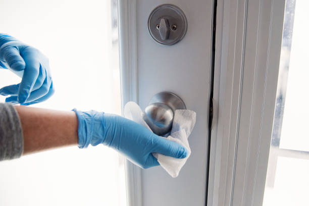 Hands with glove wiping doorknob. Female hands with blue glove wiping doorknob with disinfectant wipe. Horizontal indoors close-up with copy space. decontamination stock pictures, royalty-free photos & images
