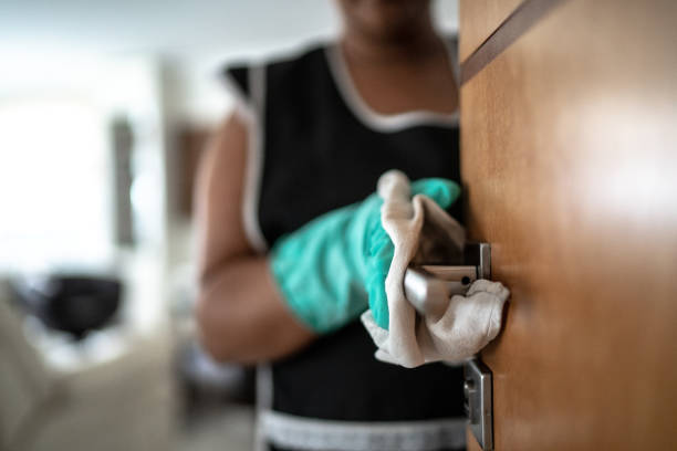 Hands with glove wiping doorknob stock photo