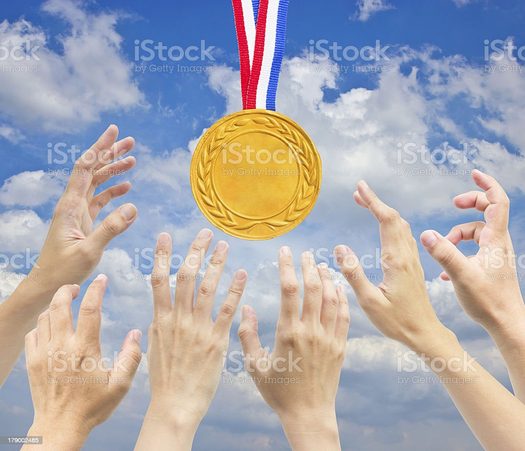 Hands with golden medal in front of blue sky. royalty-free stock photo
